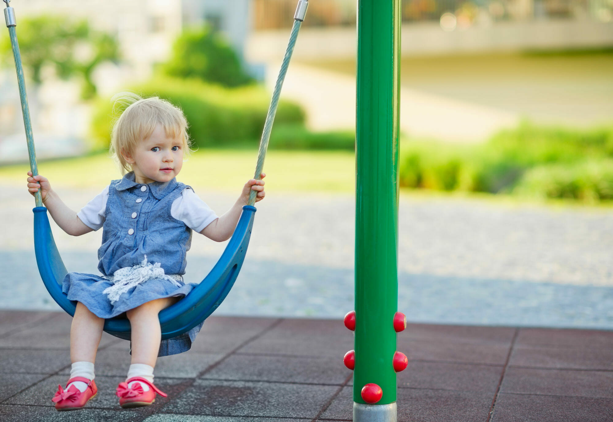 Baby Swinging On Swing On Playground Side View
